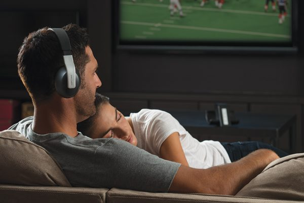 Image of a man use Headphones on his TV